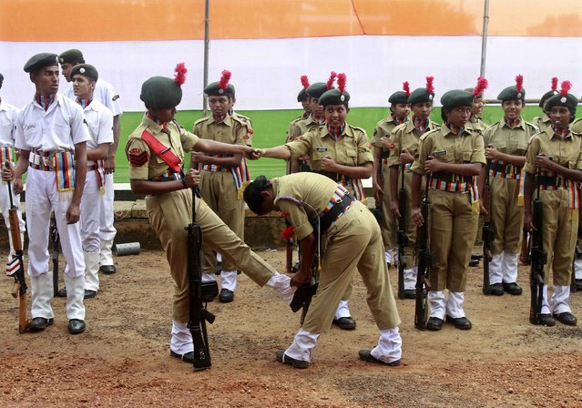 A female National Cadet Corps (NCC) cadet helps her comrade fix her boots before the start of the Independence Day parade as it rains in the southern Indian city of Kochi August 15, 2014. Indian Prime Minister Narendra Modi voiced dismay on Friday at the government in-fighting he found on assuming office in May and vowed to fire up the bureaucracy to deliver results in a country desperately in need of growth and development. (Photo by Sivaram V/Reuters)