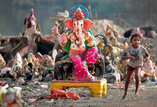 A child plays beside an idol of the Hindu god Ganesh, the deity of prosperity, the day after it was immersed in the Yamuna river for the Ganesh Chaturthi festival in Delhi, India September 6, 2017. (Photo by Cathal McNaughton/Reuters)