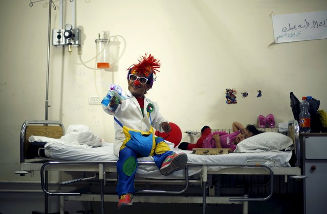 A Palestinian social activist working for the International South South Cooperation (Cooperazione Internazionale Sud Sud, or CISS) entertain children who are cancer patients inside a hospital in Gaza City August 31, 2015. (Photo by Mohammed Salem/Reuters)