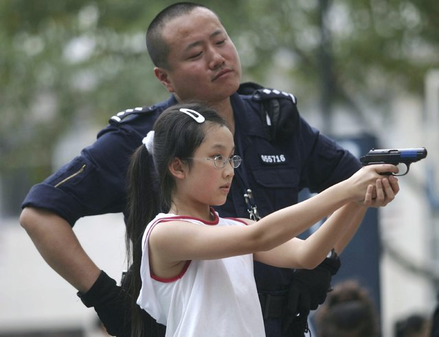 A young girl is taught how to aim a pistol by a police officer during the a Police Open Day at Shenzhen Police Training School on October 14, 2006 in Shenzhen, China. The event, displaying the latest equipment used by the police is held annually to improve the police's image and help to publicise security knowledge. (Photo by China Photos)