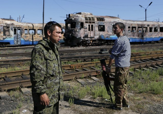 """Pro-Russian separatists stand in front of destroyed trains at a railway station in the eastern Ukrainian town of Ilovaysk August 31, 2014. Russian President Vladimir Putin called on Sunday for immediate talks on """"statehood"""" for southern and eastern Ukraine, although his spokesman said this did not mean Moscow now endorsed rebel calls for independence for territory they have seized. (Photo by Maxim Shemetov/Reuters)"""