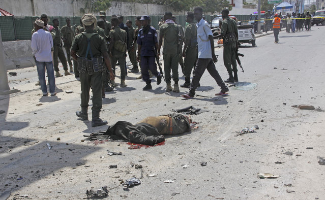 A body lies on the road as Somalis Security comb the area in a suicide car bomb attack outside The Criminal Investigation Department (CID) in Mogadishu, Somalia, Sunday, July 31, 2016. Two suicide bombers detonated an explosives-laden car outside the Criminal Investigation Department (CID) in Mogadishu, killing 9 people, including two bombers, and others were injured, a Somali police official said. (Photo by Farah Abdi Warsameh/AP Photo)
