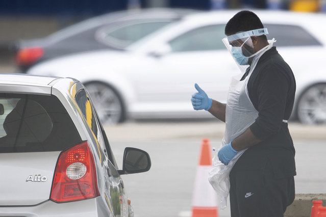 A tester, wearing a mask to protect against coronavirus, gestures to a driver at a drive through coronavirus testing site at IKEA in Wembley, north London, Thursday April 30, 2020. (Photo by Dominic Lipinski/PA Wire via AP Photo)