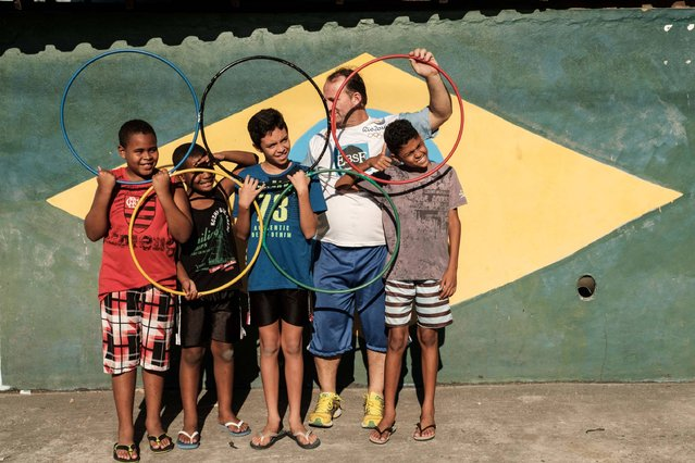 Brazilian football fan Jarbas Meneghini (2nd-R) and neighbor children pose with the Olympic rings in front of his house in Rio de Janeiro, Brazil, on July 31, 2016. (Photo by Yasuyoshi Chiba/AFP Photo)