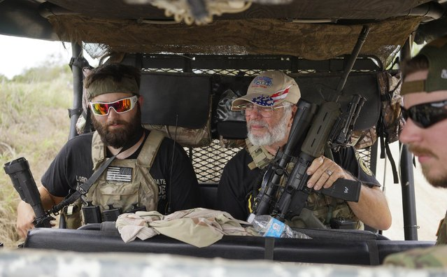 """Members of the """"Patriots"""" Huggie Bear (L, not his real name), Ray (C, no last name given) and Will (R, no last name given) patrol in their UTV near a camp of patriots near the U.S.-Mexico border outside Brownsville, Texas September 2, 2014. Huggie Bear, 25, is a former sergeant in the Army, Ray served six years in the Coast Guard and Will is a construction worker. The """"Patriots"""" are a heavily armed group who patrol the U.S. border with Mexico, trying to deter immigrants from crossing the border illegally. (Photo by Rick Wilking/Reuters)"""