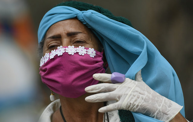 An elderly woman wearing a protective face mask and disposable gloves as a precaution against the spread of the new coronavirus, adjusts her headscarf as she takes a walk outside, breathing in fresh outdoor air, on the grounds of a nursing home in Caracas, Venezuela, Saturday, May 2, 2020. Venezuela's government allowed elderly people and children to go outdoors for a few hours, relaxing a strict quarantine to help curb COVID-19. (Photo by Matias Delacroix/AP Photo)