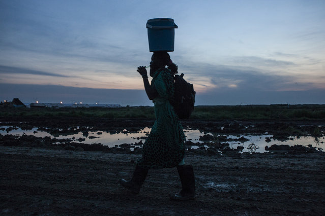 A woman brushes her teeth at dawn while leaving the camp to farm outside the Protection of Civilians (POC) site at the United Nations Mission in South Sudan (UNMISS) compound in Malakal, South Sudan on Wednesday, July 13, 2016. (Photo by Jane Hahn/The Washington Post)