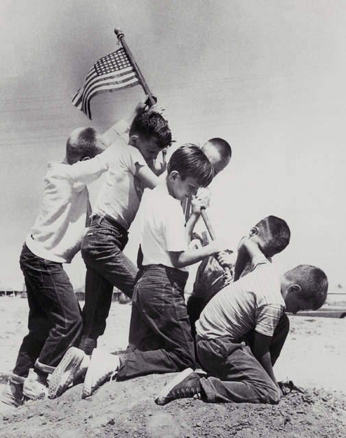 """The combination of an imaginative photographer and six neighborhood kids raising the Flag Day colors over their vacant lot fort recreates the famed Iwo Jima flag raising scene of World War II, at Lakewood Plaza, near Long Beach, Calif., June 14, 1955. The junior size """"Marines"""" are left to right: Mike McChargue, 11; Larry Hoshe 8; George Kayuck, 8; Mike Jones, 8; Dick Sandstrom, 8, and Casy Vose, 8. (Photo by AP Photo)"""