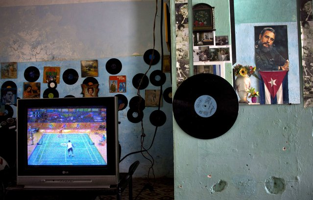 A poster with the image of the Cuban leader Fidel Castro is reflected on a mirror, right, as a TV shows the Rio Olympic Games at a house in Havana, Cuba, Saturday, August 13, 2016. (Photo by Ramon Espinosa/AP Photo)