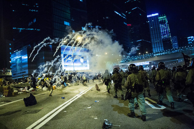 Police fire tear gas at demonstrators during a protest near central government offices in Hong Kong, China, on Sunday, September 28, 2014. (Photo by Lam Yik Fei/Bloomberg)
