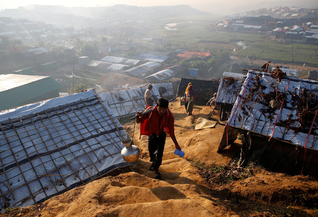 A Rohingya refugee walks uphill carrying a vessel filled with water at Palongkhali refugee camp, near Cox's Bazar, Bangladesh on November 7, 2017. (Photo by Navesh Chitrakar/Reuters)