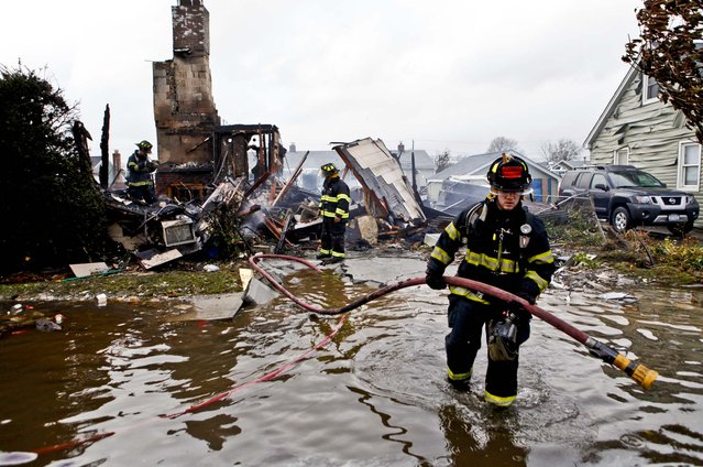 Firefighters work at the scene of a house fire in Lindenhurst, New York. According to firefighters at the scene, four homes were destroyed by fire overnight in Lindenhurst, and six in Massapequa. (Photo by Jason DeCrow/AP Photo)