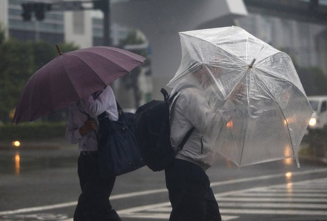 Passers-by with umbrellas struggle against strong winds and heavy rain caused by Typhoon Phanfone, in Tokyo October 6, 2014. (Photo by Issei Kato/Reuters)
