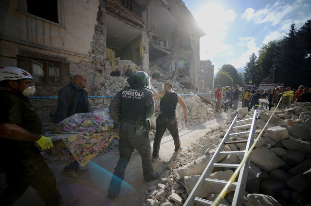 Rescuers carry the body of a victim next to the rubble of buildings in Amatrice on August 24, 2016 after a powerful earthquake rocked central Italy. The earthquake left 38 people dead and the total is likely to rise, the country's civil protection unit said in the first official death toll. Scores of buildings were reduced to dusty piles of masonry in communities close to the epicentre of the quake, which had a magnitude of between 6.0 and 6.2, according to monitors. (Photo by Filippo Monteforte/AFP Photo)