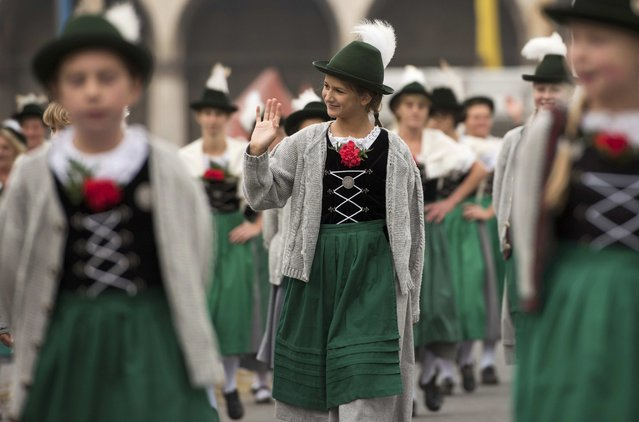 A woman dressed in traditional Bavarian clothes waves during the Oktoberfest parade in Munich, Germany, September 20, 2015. (Photo by Lukas Barth/Reuters)