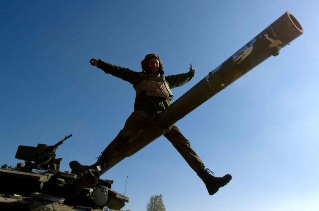 A Ukrainian serviceman gestures as he sits on a tank barrel in a basecamp near the town of Debaltseve in the Donetsk region, on October 6, 2014. The first European drones landed in Ukraine and a top US envoy visited Kiev in an urgent bid to bolster its crumbling truce with pro-Russian fighters. (Photo by Anatolii Boiko/AFP Photo)