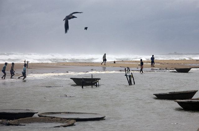 Fishermen walk along the shore at Ganjam district in Odisha October 11, 2014. (Photo by Reuters/Stringer)