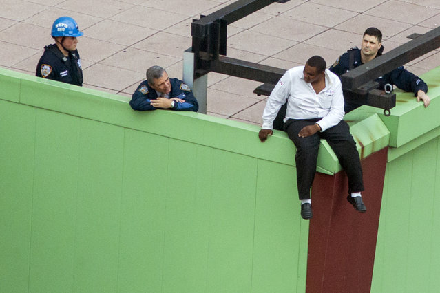 A man threatening suicide sits on a building ledge in New York's Times Square area, October 16, 2014. He was later persuaded and guided off the ledge safely by police. (Photo by Brendan McDermid/Reuters)