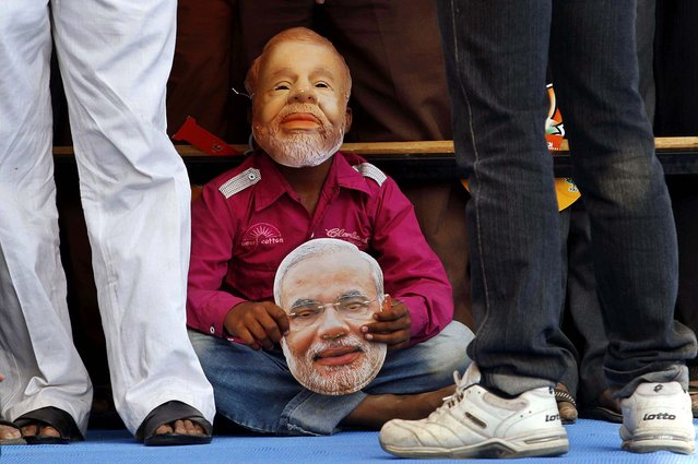 A young supporter wearing a mask of Gujarat Chief Minister Narendra Modi listens to a speech during an election campaign rally for state assembly elections at Prantij in Ahmadabad, India, December 15, 2012. The second phase of polling for the Gujarat state Assembly elections is scheduled to be held on Monday. (Photo by Ajit Solanki/Associated Press)