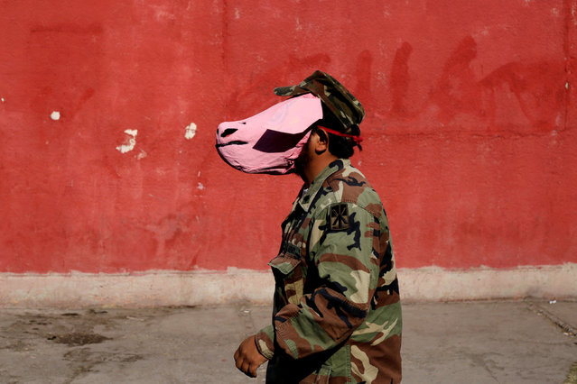 An activist dresses up as a soldier wearing a pig mask during a protest against a law that militarises crime fighting in the country in Ciudad Juarez, Mexico December 16, 2017. (Photo by Jose Luis Gonzalez/Reuters)