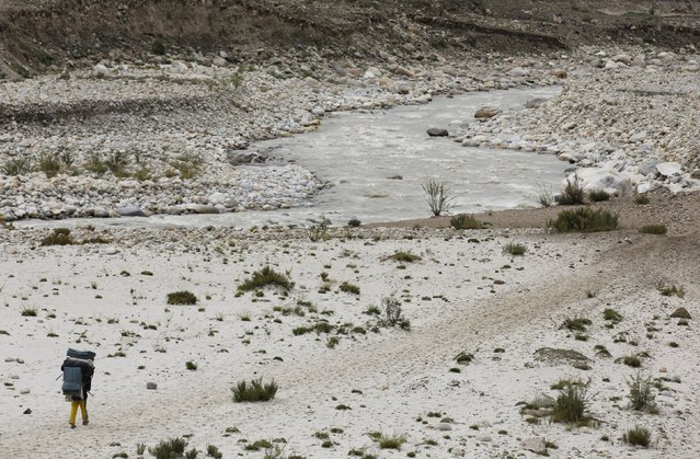A porter carries his load as he walks along a glacial river during a K2 base camp trek, near the resting point of Paju in the Karakoram mountain range in Pakistan September 10, 2014. (Photo by Wolfgang Rattay/Reuters)