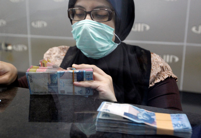 A teller in a money changer prepares Indonesian rupiah notes for a customer in Jakarta, Indonesia September 1, 2016. (Photo by Iqro Rinaldi/Reuters)