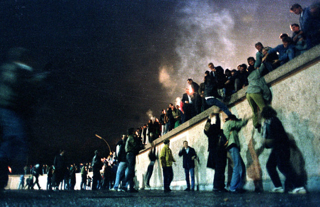 East German citizens climb the Berlin wall at the Brandeburg gate after the opening of the East German border was announced, November 10, 1989. (Photo by Reuters)