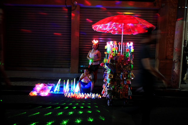 A woman and her son sells toys during the Lantern Festival celebrating the eve of the nativity of the Virgin Mary in Ahuchapan, El Salvador September 7, 2016. (Photo by Jose Cabezas/Reuters)