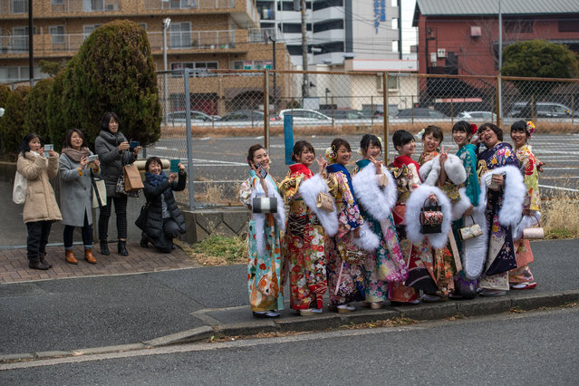 A group of women wearing kimonos look back as relatives and friends take photographs after attending a Coming of Age ceremony on January 8, 2018 in Yokohama, Japan. (Photo by Carl Court/Getty Images)
