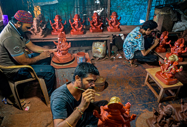 In this picture taken on August 15, 2020, Muslim potter Yusuf Zakaria Galwani (L) along with his staff, work on the idols of elephant headed Hindu god Ganesha at his workshop at Kumbharwada inside the Dharavi slums in Mumbai. - After the coronavirus pandemic clobbered his pottery business, a Muslim artisan from India's largest slum turned to a Hindu god to revive his fortunes by making environmentally-friendly Ganesha idols for an upcoming festival. In Mumbai's Dharavi slum, Galwani worked alongside his two brothers to create 13-inch tall figurines out of terracotta clay, counting on the god – who is revered as the remover of obstacles – to give his business a much-needed boost. (Photo by Indranil Mukherjee/AFP Photo)