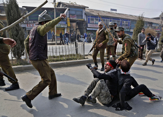 Indian policemen beat Kashmiri Shiite Muslims who took out a religious procession during restrictions in Srinagar, Indian-controlled Kashmir, Sunday, November 2, 2014. Police imposed restrictions in some parts of Srinagar fearing religious processions marking the Muslim month of Muharram, would turn into anti-India protests. Large public gatherings have been banned in Indian Kashmir since the outbreak of an armed insurgency against Indian rule in 1989. (Photo by Mukhtar Khan/AP Photo)