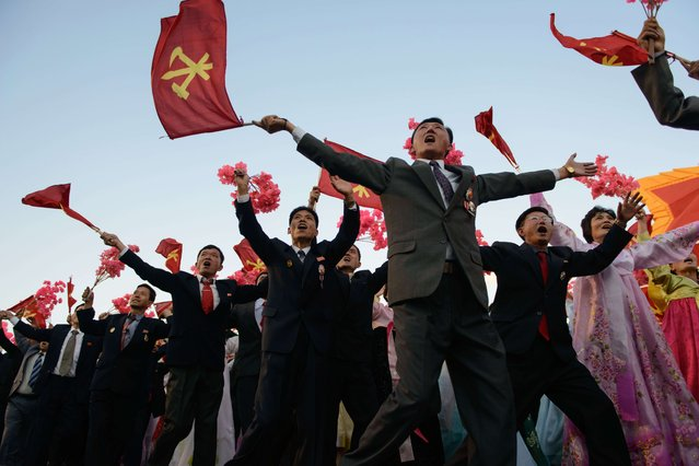 Participants wave flowers towards North Korean leader Kim Jong-Un (not pictured) as they pass through Kim Il-Sung square during a mass military parade in Pyongyang on October 10, 2015. (Photo by Ed Jones/AFP Photo)