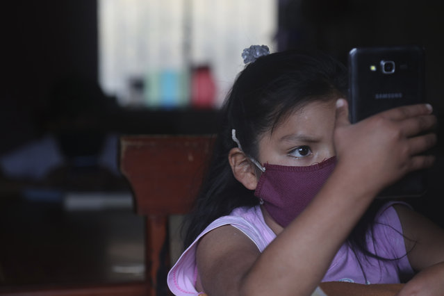 Alison Quinotoa eyes her cell phone as she receives classes via the internet, at her home in La Josefina, Ecuador, Thursday, September 3, 2020. Because of the unabated COVID-19 pandemic, Ecuador has started the new school year imparting classes via the internet. (Photo by Dolores Ochoa/AP Photo)