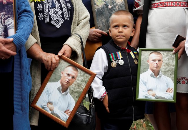 Relatives hold portraits of Ukrainian serviceman, who was killed in the conflict in eastern Ukraine, during a rally to commemorate the 6th anniversary of the Battle of Ilovaisk, ahead of the Day of Remembrance of Ukraine's Defenders, in front of the Russian embassy in Kyiv, Ukraine on August 28, 2020. (Photo by Valentyn Ogirenko/Reuters)