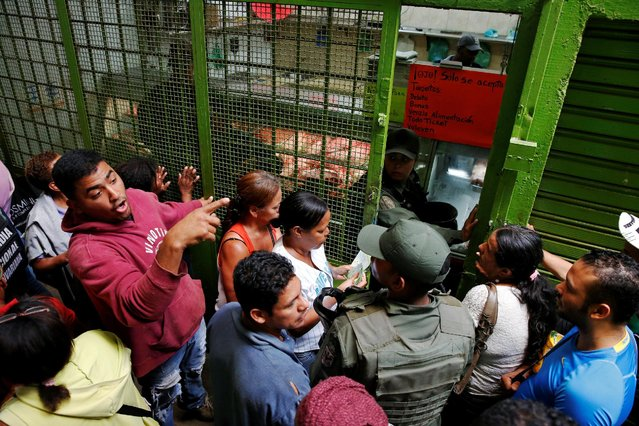 Venezuelan soldiers control the crowd as people queue trying to buy basic food during a special inspection to a municipal market in Caracas, Venezuela July 15, 2016. (Photo by Carlos Garcia Rawlins/Reuters)