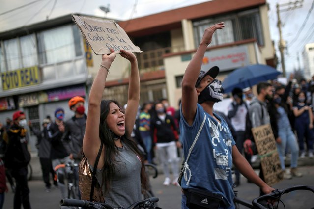 """People protest outside a police station after a man, who was detained for violating social distancing rules, died from being repeatedly shocked with a stun gun by officers, according to authorities, in Bogota, Colombia on September 10, 2020. The sign reads: """"Who takes care of us from the police"""". (Photo by Luisa Gonzalez/Reuters)"""