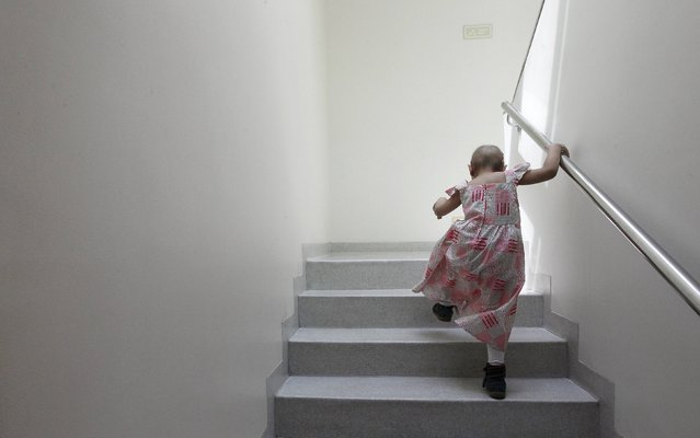 Alexandra Munoz, 5, who lost her hair due to chemotherapy to treat a malignant brain tumor, climbs stairs in the cancer ward of the Luis Calvo Mackenna Hospital in Santiago October 20, 2014. The wigs, handmade by Italian-Chilean hair stylist Marcelo Avatte and his team, have helped the children regain their self-esteem and confidence during cancer treatment. (Photo by Rodrigo Garrido/Reuters)