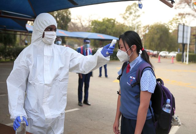 A medical worker checks the temperature of a student at Gateway Secondary school in Harare, Zimbabwe, on September 15, 2020. Zimbabwe has opened up most of its sectors including industry, commercial, aviation and tourism after months of closure due to the lockdown. In the education sector, only examination classes have been given the nod to reopen. (Photo by Shaun Jusa/Xinhua News Agency)
