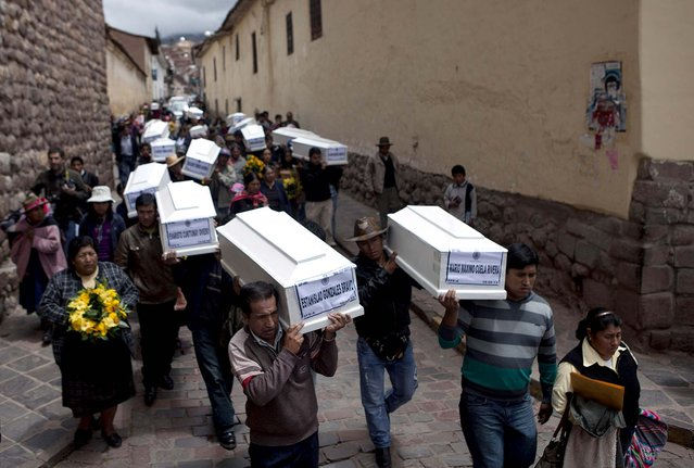 Coffins containing the remains of people whose bodies were excavated are carried to a church in Cuzco, Peru, February 19, 2013. Authorities turned over to families 26 coffins containing the remains of people from various towns whose body parts were excavated from 250 graves since November. According to Peruvian authorities, the victims, including women, children and village authorities, were killed by members of both the Shining Path militant group and the army between 1980 and 2000, and are among tens of thousands of Peruvians who died during the Maoist-inspired insurgency. (Photo by Martin Mejia/Associated Press)