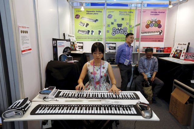 A woman demonstrates a foldable music keyboard during the China Import and Export Fair, also known as Canton Fair, in the southern Chinese city of Guangzhou October 15, 2015. (Photo by Bobby Yip/Reuters)
