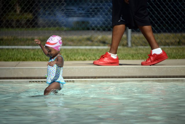 As her father walks behind her, Addison Keller, 2, enters the MacKay Park pool in Englewood, NJ for a swim lesson on July 23, 2016. (Photo by Carmine Galasso/The Record of Bergen County via AP Photo)