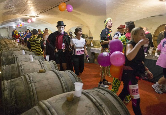 Costumed competitors taste wine as they run in the cellar at the castle of Pizay as they participate in the Marathon International du Beaujolais race, November 22, 2014. (Photo by Robert Pratta/Reuters)