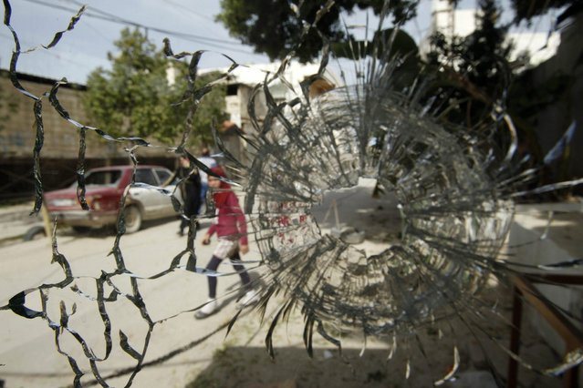 A girl is pictured through a broken window after clashes at Ain al-Hilweh Palestinian refugee camp near the port city of Sidon in south Lebanon March 12, 2013. Ten people were wounded and one killed during clashes between the Fatah movement and radical Islamists that started on Monday. (Photo by Ali Hashisho/Reuters)
