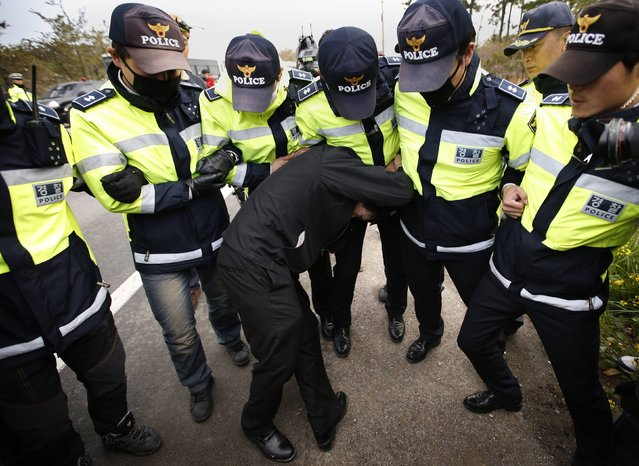 A family member of a passenger missing after the South Korean Sewol ferry capsized is blocked by police during a protest in Jindo calling for a meeting with South Korean President Park Geun-hye and demanding the search and rescue operation be speeded up, in this April 20, 2014 file photo. (Photo by Kim Kyung-Hoon/Reuters)