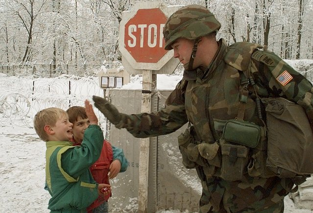 U.S. Army Lt. William Donovan, of Rumson, N.J., speads some holiday goodwill as he gives a high five to a Bosnian schoolboy outside the front gate of Tuzla Airbase, Friday, December 29, 1995. Soldiers stationed at the gates have become a major curiosity for local children. (Photo by John Gaps III/AP Photo)