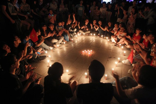 Students gather around candles during Earth Hour in Hanoi March 23, 2013. Earth Hour, when everyone around the world is asked to turn off lights for an hour from 8.30 p.m. local time, is meant as a show of support for tougher action to confront climate change. (Photo by Kham/Reuters)