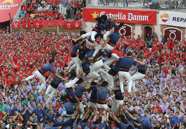 "Capgrossos de Mataro team members fall during the 25th Castells' contest at the Tarraco Arena in Tarragona, Catalonia, northeastern Spain, 02 October 2016. The ""Castells"" is a popular event in which people create human towers up to a height of between six and ten levels. (Photo by Jaume Sellart/EPA)"
