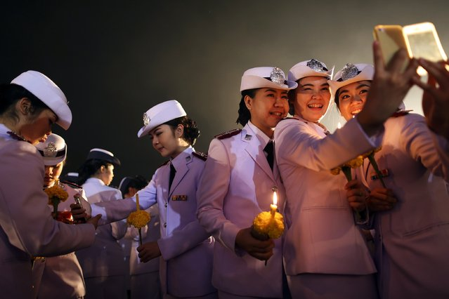 Military cadets take pictures of themselves during a ceremony celebrating the birthday of Thailand's King Bhumibol Adulyadej outside the Grand Palace in Bangkok December 5, 2014. King Bhumibol canceled a public appearance on his 87th birthday on Friday on the advice of doctors, disappointing thousands outside a hospital where he is staying, hoping for a glimpse of the world's longest-reigning monarch. (Photo by Damir Sagolj/Reuters)