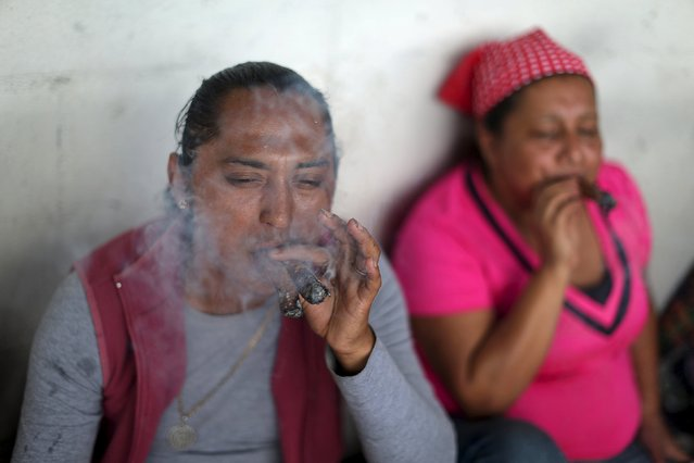 People smoke tobacco outside the church of San Simon in Iztapa, in Chimaltenango, Guatemala October 28, 2015. (Photo by Jorge Dan Lopez/Reuters)