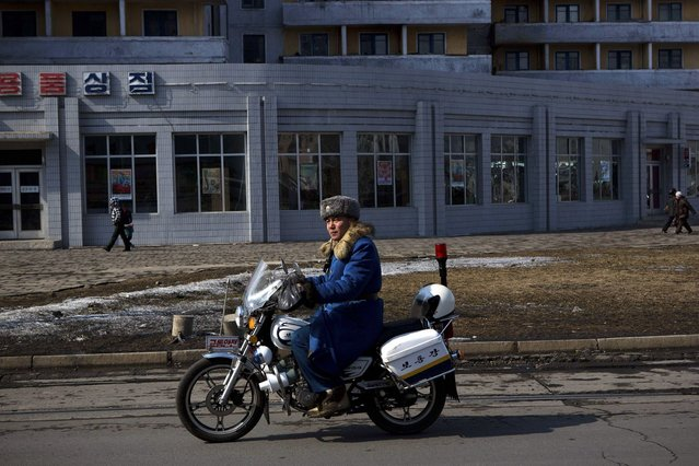A North Korean traffic policeman on a motorcycle patrols a street in central Pyongyang, North Korea on Friday, February 22, 2013. (Photo by David Guttenfelder/AP Photo)